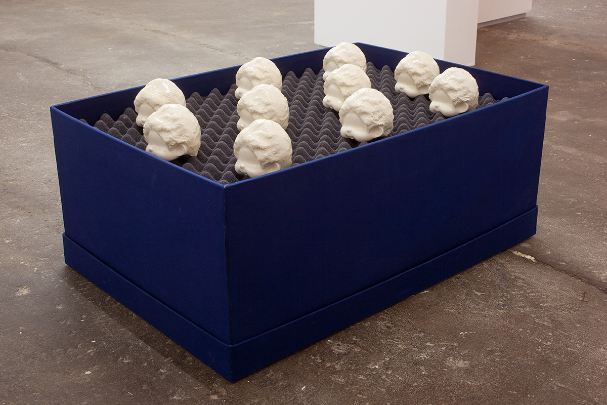 モンチッチ 頭部, 2012. Ten glazed, porcelain slip casts, foam, buckram covered box. 21 x 17 x 21 inches.