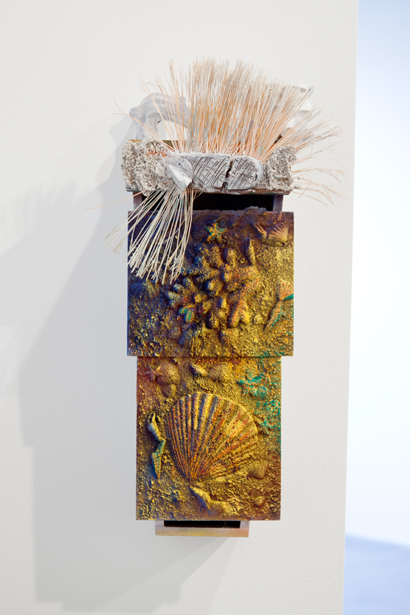 Caught by the Ripe Fruit Cop, 2012. Enamel spray paint, sand, acrylic, ink, bristles, wood. 18 ½ x 6 x 4 ½ inches.