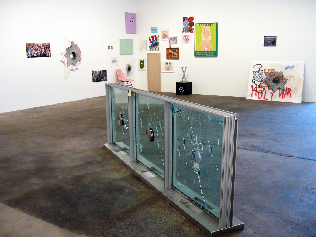 Axis of Praxis, installation view. Foreground: Nate Lowman, Not Sorry, 2006. Bullet-resistant glass, brushed stainless steel, and stickers. 36 inches x 12 inches x 108 ½ inches.
